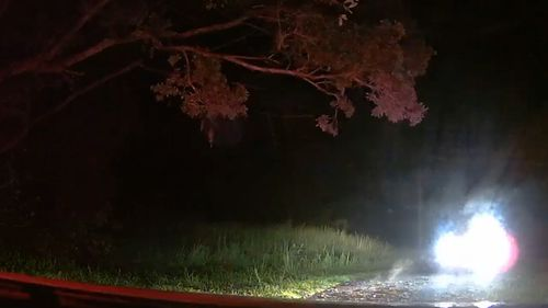 The headlights of a stolen vehicle approach the police car at speed after driving through a gate on private property.