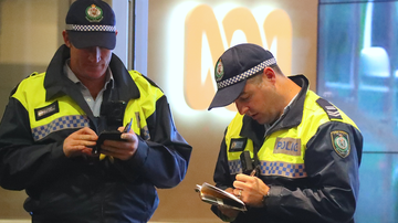 Two policemen stand in front of an ABC logo at the main entrance to the ABC building located at Ultimo in Sydney, Wednesday, June 5, 2019.