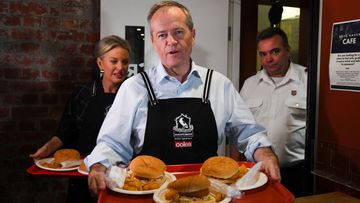 Bill Shorten and his wife Chloe serve food during a visit to the Salvation Army's Lighthouse Cafe in Melbourne on Friday.