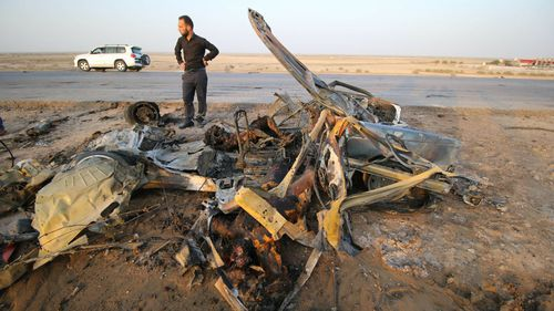 An Iraqi man inspects a wrecked vehicle after Daesh carried out a terror attack with a bomb-laden vehicle following the attack to a restaurant. (AFP)
