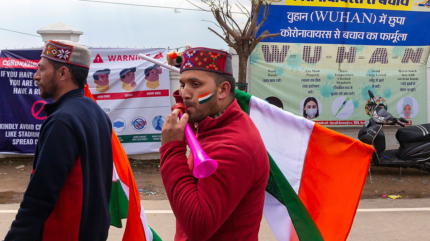 Indian fans walk past hoardings informing prevention of COVID-19 as they arrive to watch the first one-day international cricket match between India and South Africa in Dharmsala, India
