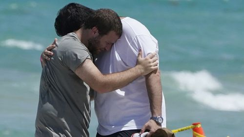 Two men console each other on the beach near the site of the Champlain Towers South condo tower in Florida.