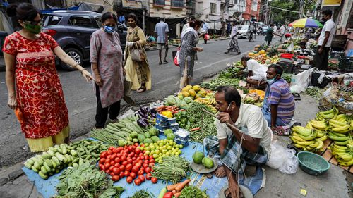 People wearing masks to prevent the spread of the coronavirus buy vegetables from pavement stalls  in Kolkata. India now has the second most COVID-19 cases of any country in the world.