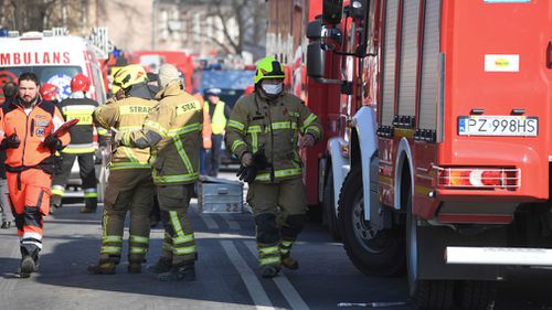 Firefighters and rescuers work at the scene of a building collapse. (AAP)