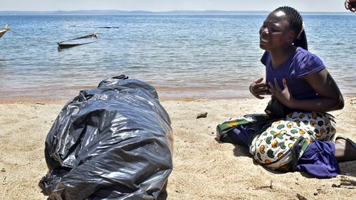 A woman cries beside the body of her sister, a victim of the MV Nyerere passenger ferry, as she awaits transportation for burial on Ukara Island, Tanzania. (AAP)