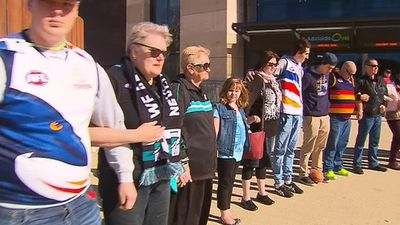 Fans standing together in silence outside the oval. (9NEWS)