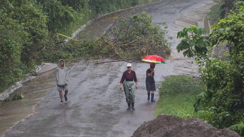 Neighbours walk under the rain past a washed out road in Alajuelita on the outskirts of San Jose, Costa Rica. (AP)