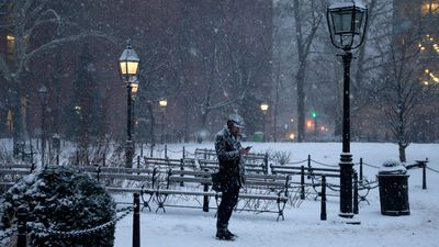 A man checks his phone as he walks through Washington Square Park during a winter storm in New York. (AAP)