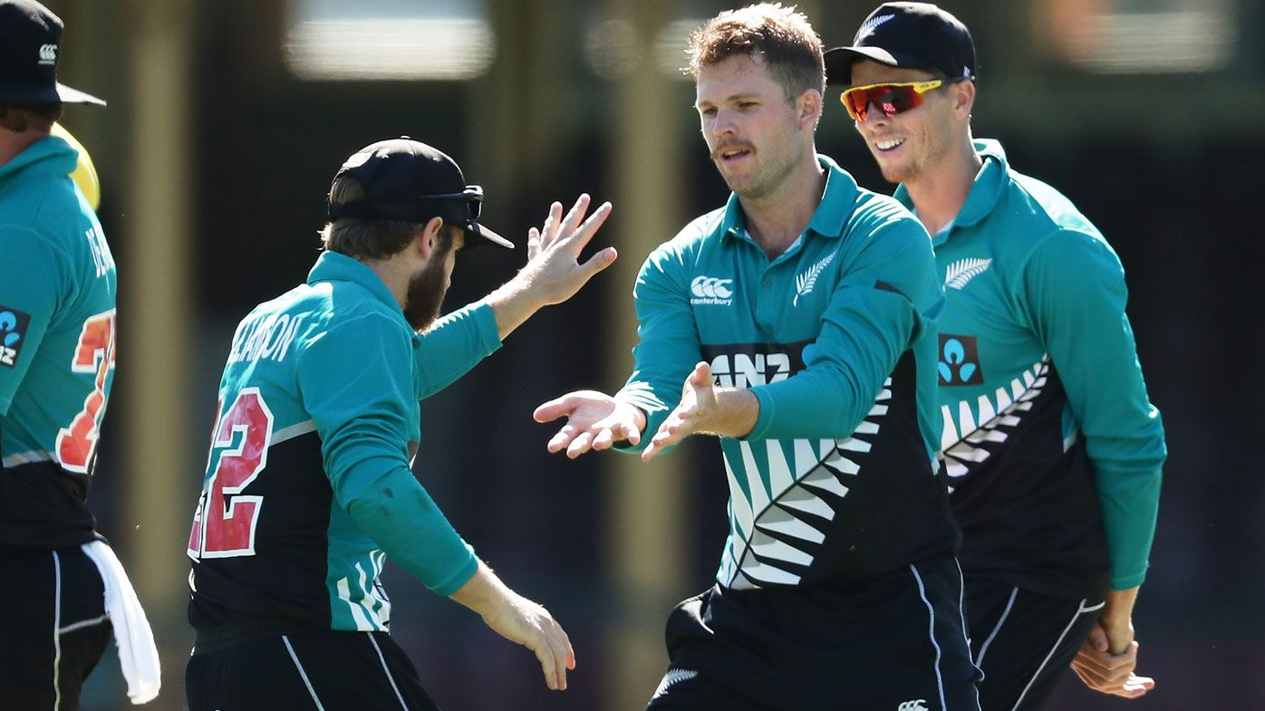 Lockie Ferguson of New Zealand celebrates with team mates after taking the wicket of David Warner