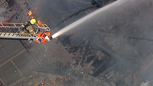 A firefighter attacks the fire from above. (9NEWS)