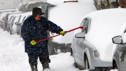 A man usues a mop to clear snow from his car in Old Drumchapel, Glasgow, Scotland. (AAP)