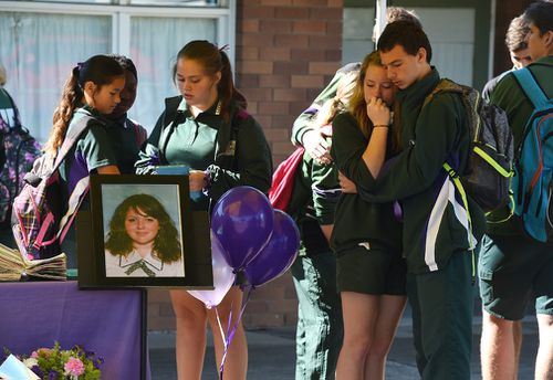 Friends comfort each other during the memorial service. (Image: AAP)