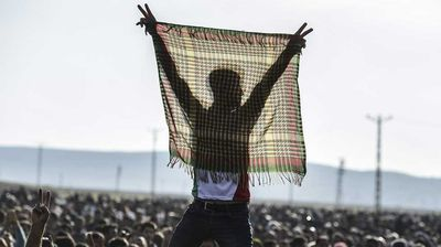 A man flashes the V for victory sign during a celebration rally near the Turkish-Syrian border at Suruc.