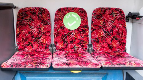 A green sticker shows where people can sit on buses across the NSW train and bus network.