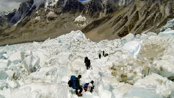 Trekkers seen here are making their way through the treacherous Khumbu Icefall, just above Everest base camp. The new route will take climbers through the centre of this area. (AAP)