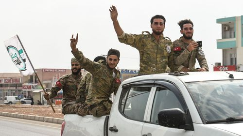 Members of Turkish-backed Free Syrian Army wave on top of a vehicle as they drive back to their base camp on October 16, 2019 in Akcakale, Turkey.
