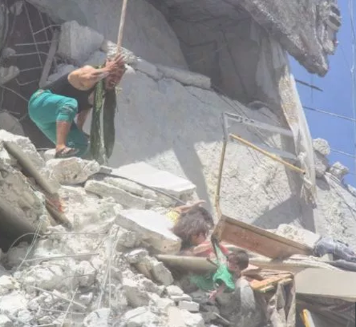 Their father looks on with horror at his two young daughters, teetering on the destroyed edge of a bombed building. One girl grabs the shirt of her infant sister, trying to save her from falling from the rubble.