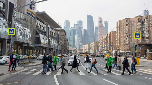 Pedestrians cross a street in front of skyscraper office buildings situated in the Moscow International Business Centre.