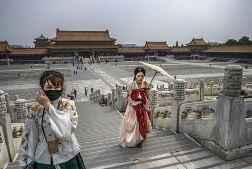 Chinese women dressed in traditional costume known as Hanfu tour the Forbidden City, which recently re-opened to limited visitors, in Beijing, China