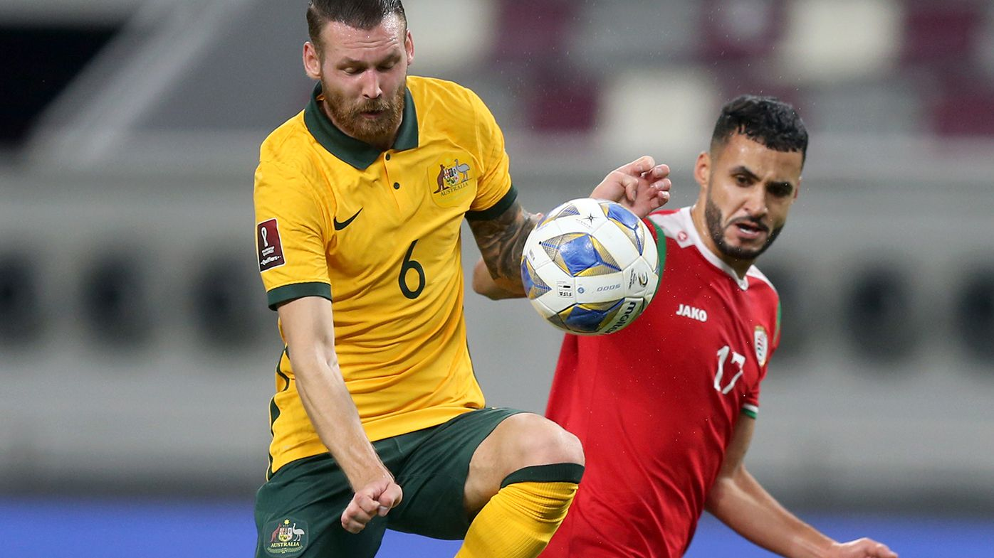 Martin Boyle of Australia and Ali al-Busaidi of Oman battle for the ball during the 2022 FIFA World Cup Qualifier.