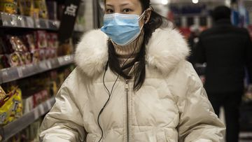 A woman wears a protective mask as she shops in the supermarket on in Wuhan, Hubei province, China.