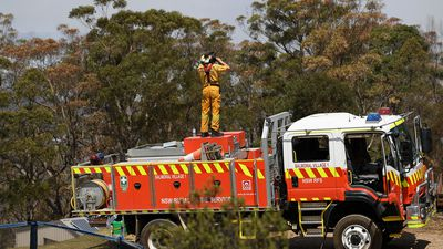 NSW Rural Fire Service crews watch on as water bombing helicopters fight a fire burning in bushland at Penrose in the NSW Southern Highlands, 165km south of Sydney, Friday, January 10, 2020.