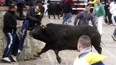 A second unidentified man is gored by a bull during an 'encierro' (running of the bulls) on Saturday. (AAP)