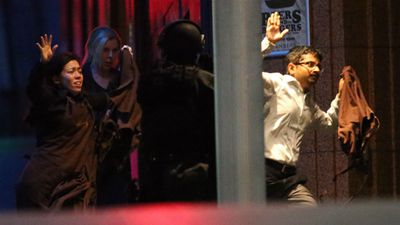 The hostages held their hands in the air as they ran from the cafe. (AAP)
