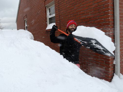 Patrick Harden clears snow from the roof of his car. (AAP)