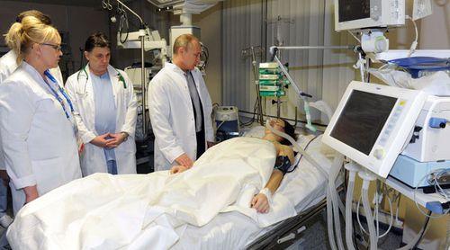 President Vladimir Putin visits Russian freestyle skier Maria Komissarova in a hospital in Sochi on February 15, 2014. (Getty)