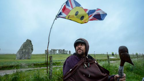 People participate in the morning sunrise ritual in the rain at Stonehenge on June 21.