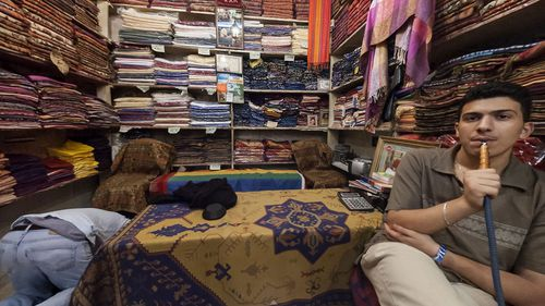A young man smokes as another prays inside their market store selling fabrics. (Photo: Willy Kaemena)