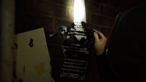 The video then cuts to Banksy as he creates the artwork on the wall of Reading Prison.