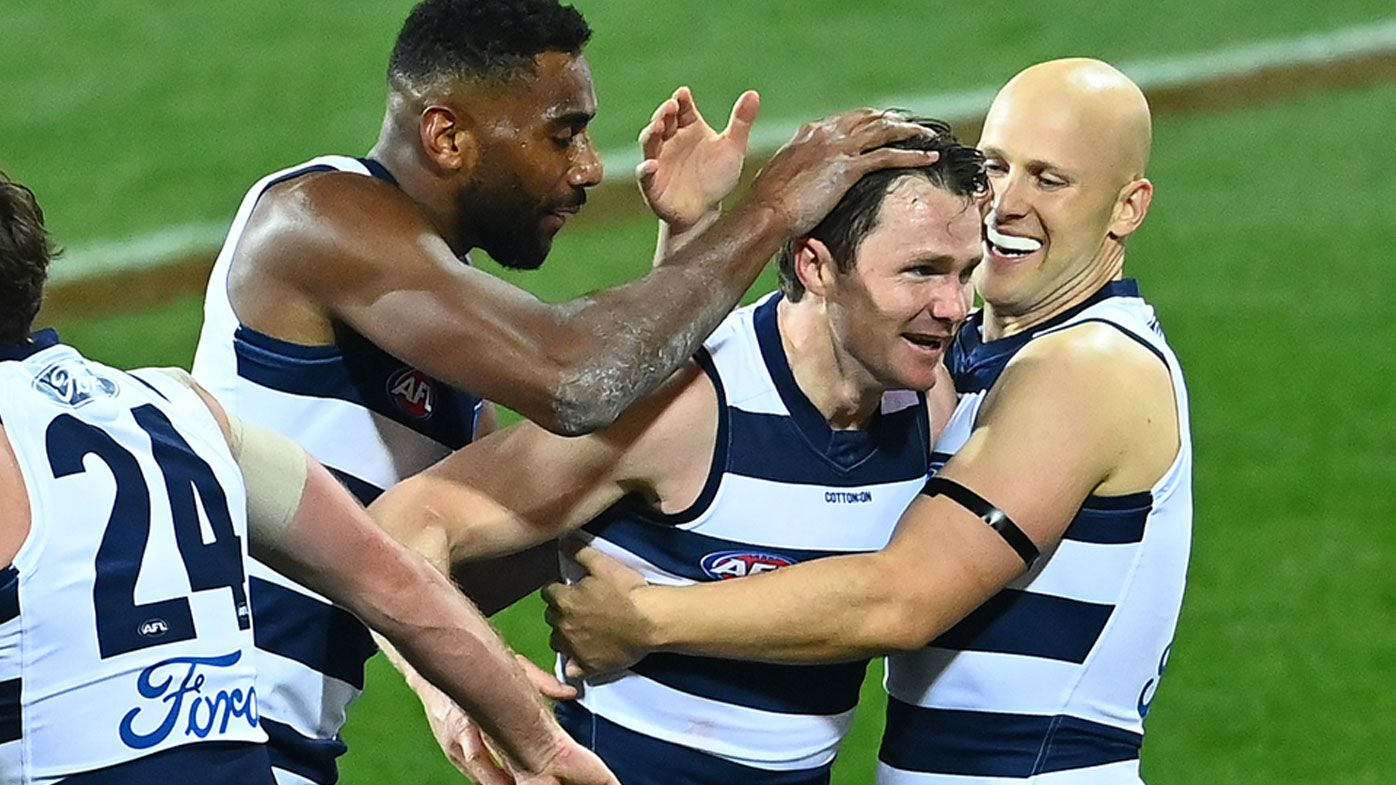 Patrick Dangerfield of the Cats is congratulated by team mates after kicking a goal