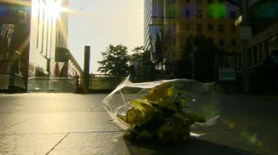 A single bunch of flowers sits near the Lindt Cafe as the sun rises following last night's siege. (Supplied