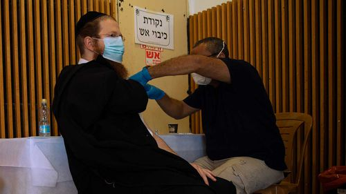 An ultra-Orthodox Jewish man receives a Pfizer-BioNTech coronavirus vaccine at a COVID-19 vaccination center in the West Bank Jewish settlement of Givat Zeev, near Jerusalem.