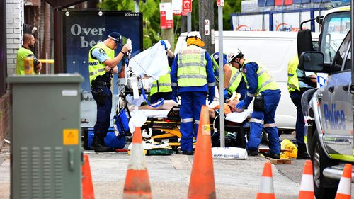 Paramedics work to stabilise one patient following a horrific truck crash in Sydney's south.
