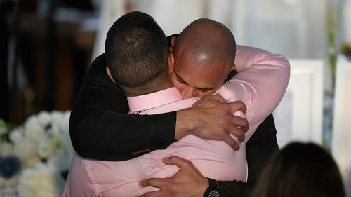 Danny Abdallah is comforted during the funeral for his children.