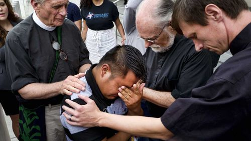 Father Tom Carey, left, is joined by Rev. David Farley and Rev, Matthias Peterson-Brandt, right, as they pray over Hermelindo Che Coc. (AAP)