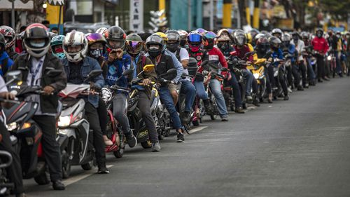 Motorcyclists outside Manila queue up for a health check before they are allowed into the city.