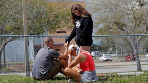 A family prays outside Marjory Stoneman Douglas High School in Parkland, Florida following the shooting.