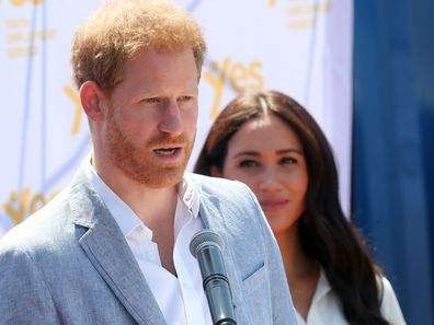 Prince Harry delivers a speech during the royal tour of Africa while wife Meghan Markle looks on.
