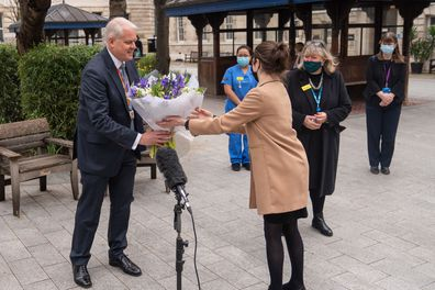 Chief Executive of St Bartholomew's Hospital Professor Charles Knight receives flowers from Queen Elizabeth II during a ceremony at St Bartholomew's Hospital, London on the anniversary of the first national lockdown to prevent the spread of coronavirus. (Photo: March 23, 2021)