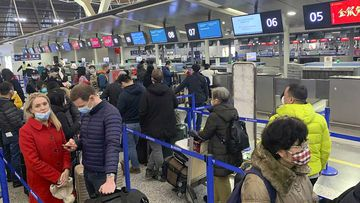 Travellers wearing face masks stand in line at the check-in counters for Cathay Pacific at Shanghai Pudong International Airport in Shanghai.