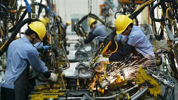 Factory workers assemble vehicle parts on an assembly line