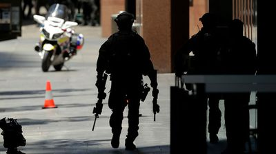 An armed policeman on Philip St walking towards Martin Place. (Getty)