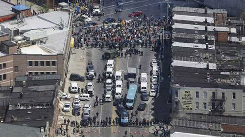In this aerial photo, police stand in formation near a gathering of protesters at the intersection of North Avenue and Pennsylvania Avenue in Baltimore. (AP)