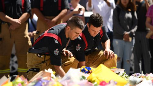 Firefighters leave flowers at the corner of Bourke and Elizabeth streets. (9NEWS)