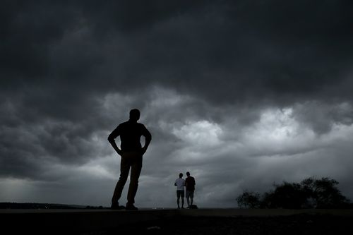 People watch from the Liberty Memorial as a severe storm that dropped several tornados earlier approaches downtown Kansas City, Mo.
