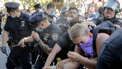 New York Police officers use pepper spray on protesters during a demonstration Saturday, May 30, 2020, in the Brooklyn borough of New York. Protests were held throughout the city over the death of George Floyd, a black man who was in police custody in Minneapolis. Floyd died after being restrained by Minneapolis police officers on Memorial Day. (AP Photo/Seth Wenig)